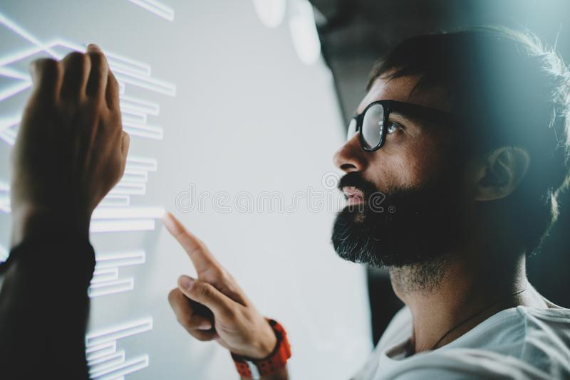 Concept of virtual panel display,diagram,digital graph interfaces.Young bearded man touching virtual panel with graphs stock photo