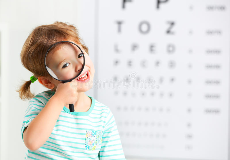 Concept vision testing. child girl with a magnifying glass stock photography
