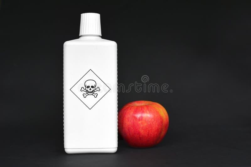 Concept voor gebruik van gevaarlijke pesticiden in landbouwvoedingsmiddelen met rode appel naast witte fles met giftige waarschuw stock afbeeldingen