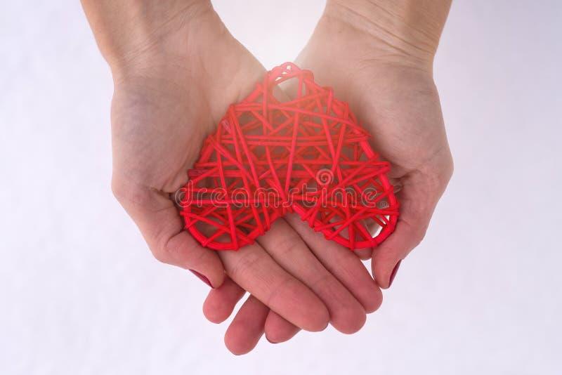 Concept voor Valentine& x27; s Dag, huwelijk: handen die een rood hart houden stock foto