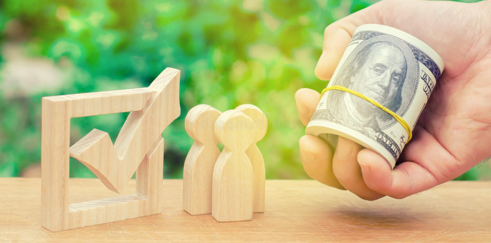Concept of voting and democratic elections. Corruption and bribery of voters. Voters cast their votes for money. Referendum.A hand. Is holding out money to royalty free stock image