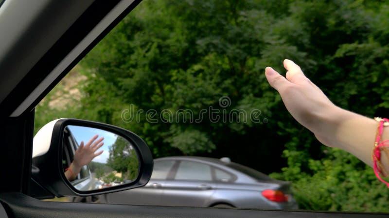 Concept vrijheid, autotravel en avontuur Een vrouwenbestuurder voelt de wind door haar handen terwijl het drijven langs een weg stock foto