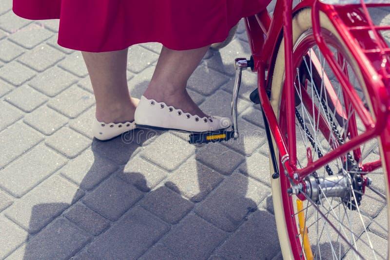 Concept: vrouwen op een fiets Het meisje in de rode rok zet zijn voet op het fietspedaal Een deel van het beeld royalty-vrije stock afbeeldingen