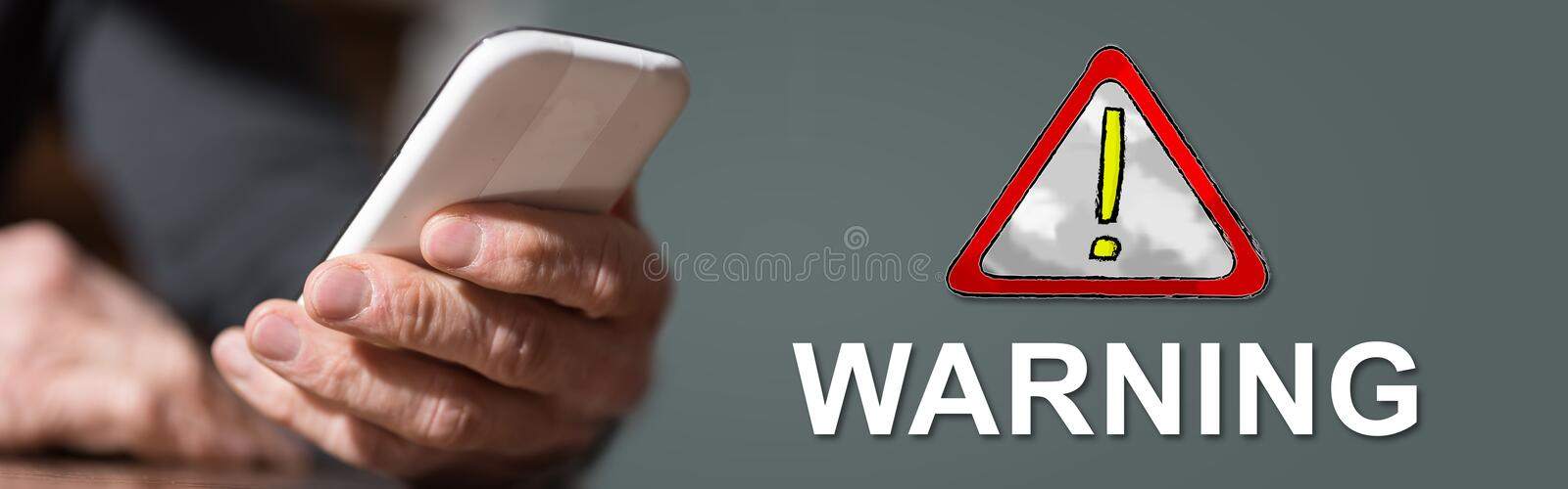Concept of warning. Hand holding mobil phone with warning concept on background stock photography