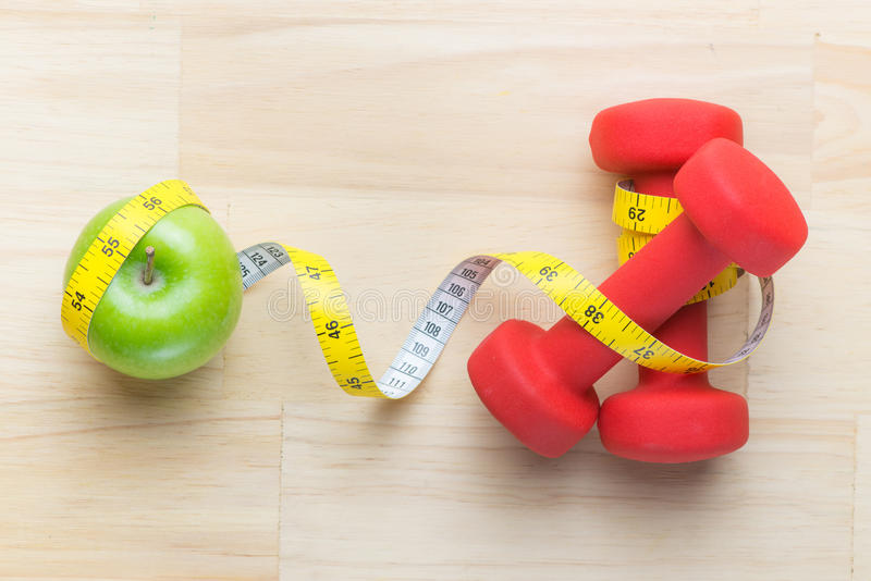 Concept of weight loss with fresh green apple, measuring tape and dumbbells. Fitness diet programme. Top view angle with copy stock image