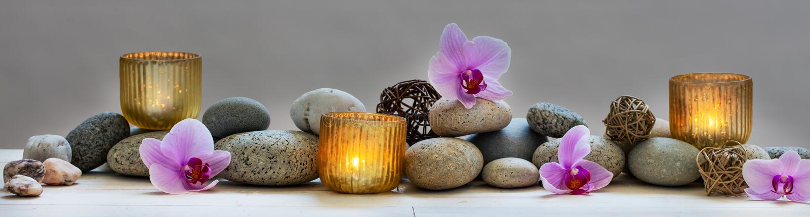 Concept of wellbeing with pebbles, orchids and candles, panoramic. Concept of spa, massage, yoga, wellbeing or feng shui with mineral pebbles, fresh orchid royalty free stock images