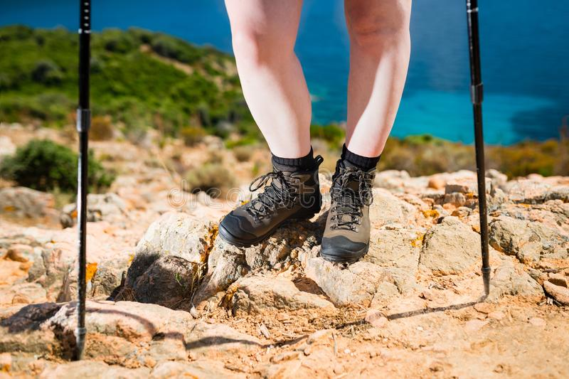 Concept of woman feet in hiking boots on the trail on the rocks above the blue ocean. The active way to spend the summer holidays stock photo