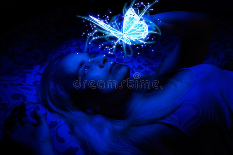 Concept of a woman laying in bed in the dark, illuminated with blue light from floating magical butterfly. Above her, her hand lightly touching it stock images