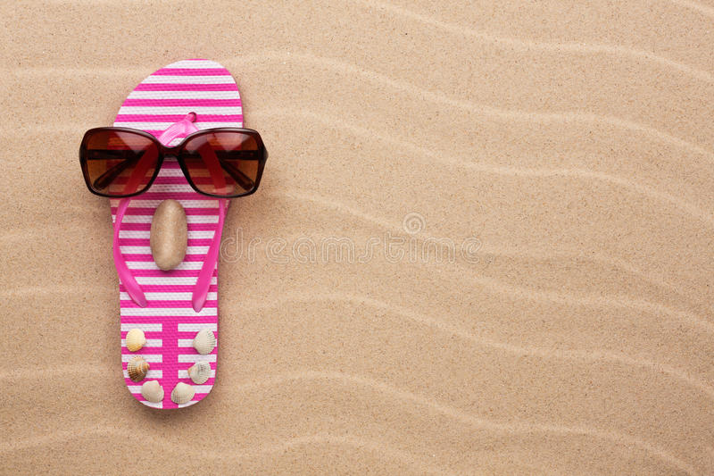 Concept of a woman's face, flip-flops and sunglasses. On wavy in sand stock images