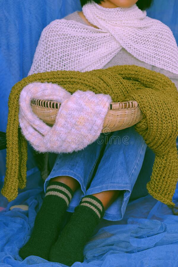 Concept woman wear blue jeans, white woolen sweater, sock, white and moss green wool scarf on blue background royalty free stock photo