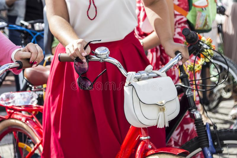 Concept: women on bicycles. Hands holding the handlebars. In his right hand sunglasses. White bag on the steering wheel royalty free stock image