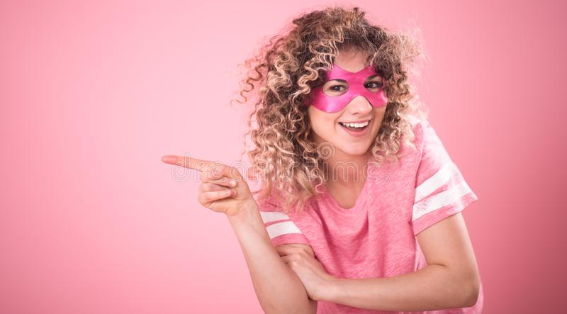 The concept of women, a portrait of a superhero girl. Women concept, Portrait of beautiful curly-haired young girl in superhero mask shows finger to the side, in stock images