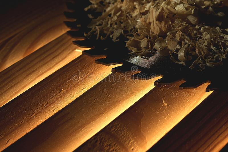 The concept of work as a carpenter - Wood chips and disk circular saw. Circular circular saw lies on a glowing dark wooden background royalty free stock image