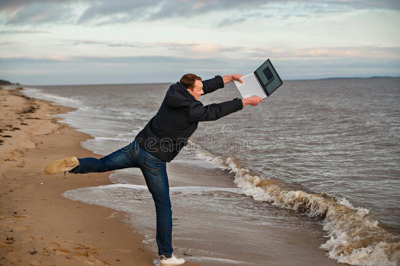 Concept work and rest issues. Man freelancer throws laptop in the sea. stock images