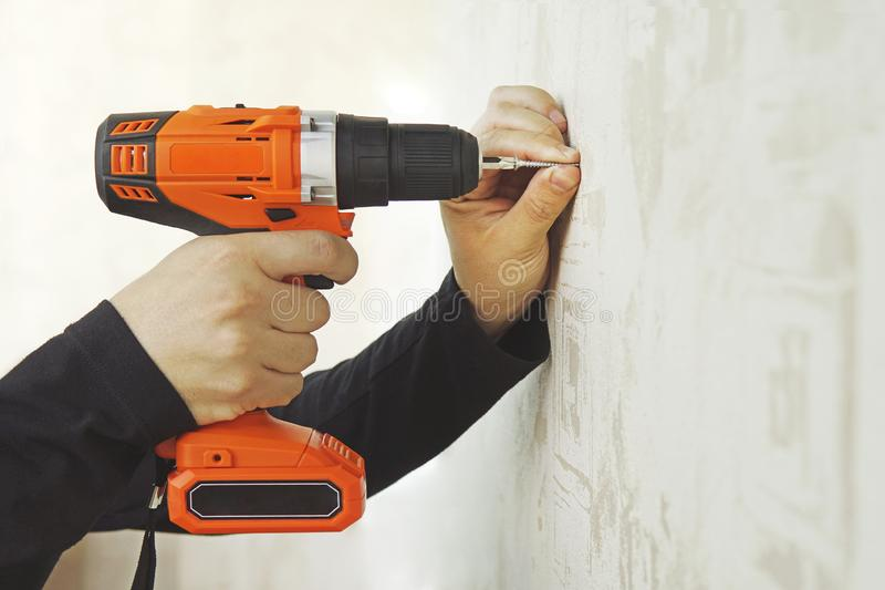 Concept. Worker is screwing the drywall screw by screw gun to plasterboard wall in apartment is under construction, remodeling, stock images