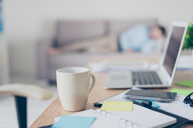 Concept of working all day and night long. Close up photo of white cup of coffee standing on desk near notes and laptop, tired de stock photo