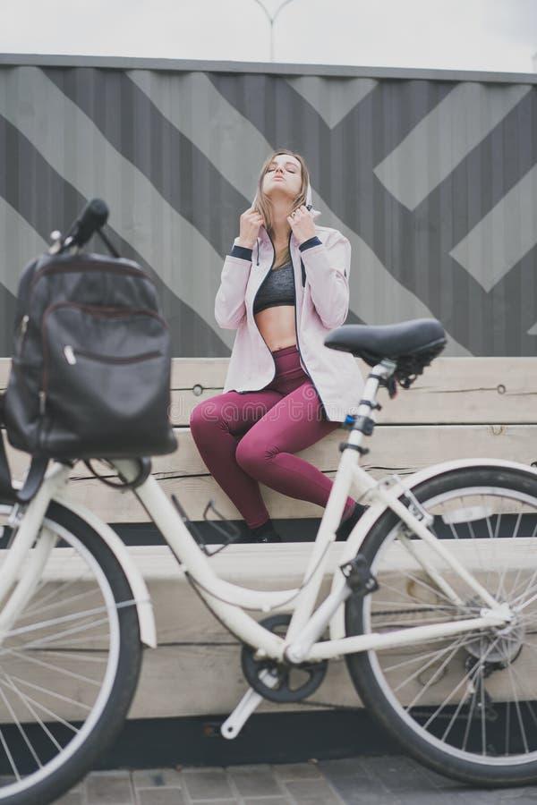 Concepte do esporte do estilo de vida Jovem mulher 'sexy' com a bicicleta do vintage no estacionamento da cidade Cor da natureza  fotos de stock