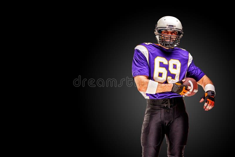 Concepten Amerikaanse voetbal, portret van Amerikaanse voetbalster in helm met patriottische blik Zwarte witte achtergrond royalty-vrije stock foto's