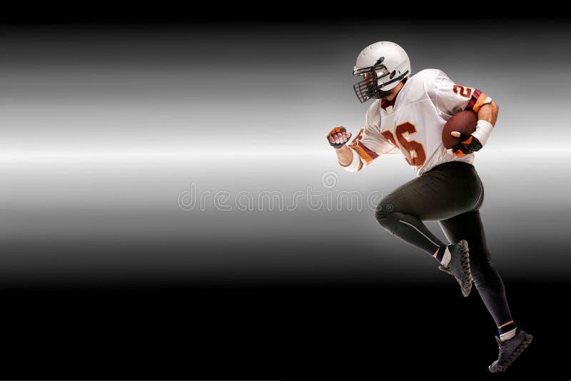 Concepten Amerikaanse voetbal, Amerikaanse voetbalster met in hand bal Zwarte witte achtergrond, exemplaarruimte amerikaans stock foto