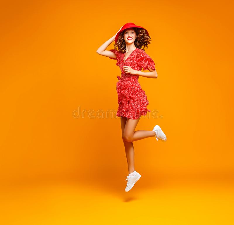 Concepten gelukkige emotionele jonge vrouw in rode de zomerkleding en hoed die op gele achtergrond springen stock afbeeldingen