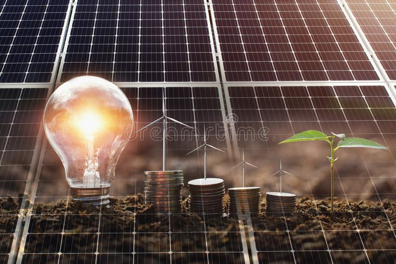 concepten schone energie en besparingsmacht in aard zonnepaneel met windturebine op geld en lightbulb royalty-vrije stock fotografie