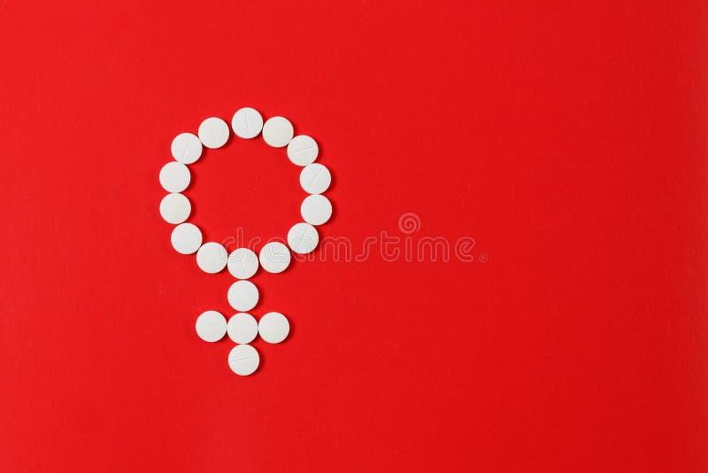 Concepten Vrouwelijke gezondheid Geslachtssymbool van de witte rode achtergrond die van pillentabletten wordt gemaakt royalty-vrije stock afbeeldingen