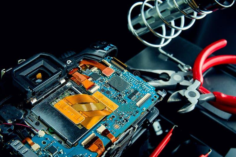 Conceptendemontage en reparatie van digitaal SLR-cameraclose-up op zwart glas met hulpmiddelen stock afbeelding