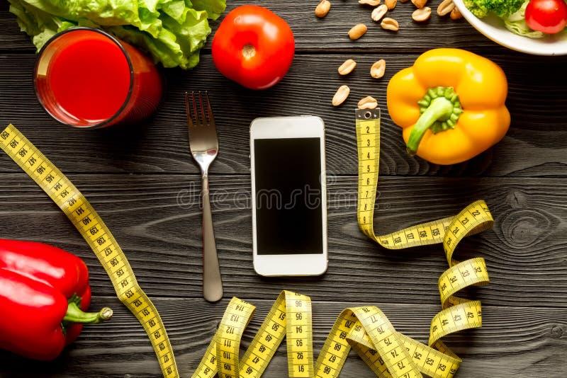 Conceptendieet en smartphone met groenten omhoog spot royalty-vrije stock afbeeldingen