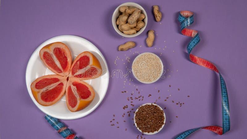 Conceptendieet - gezond voedsel met grapefruit, pinda, sesam, lijnzaad en het meten van band op purpere achtergrond royalty-vrije stock afbeelding