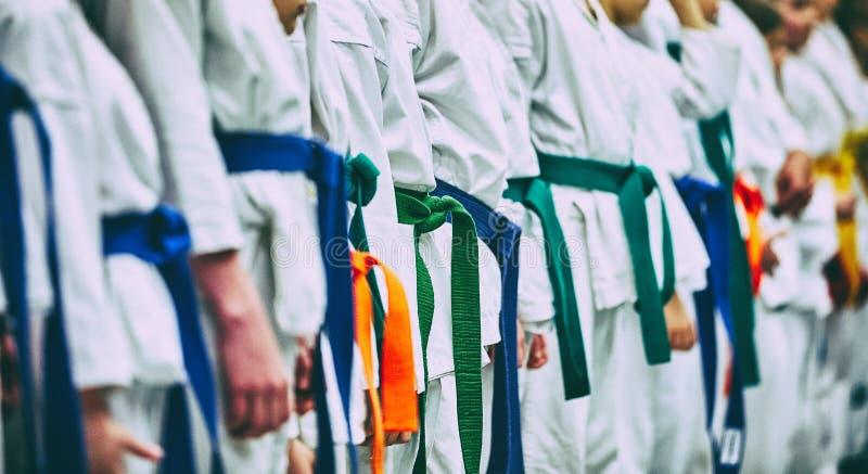 Conceptenkarate, vechtsporten Bouw van studenten in de zaal alvorens op te leiden Kimono, verschillende verschillende riemen, stock afbeeldingen