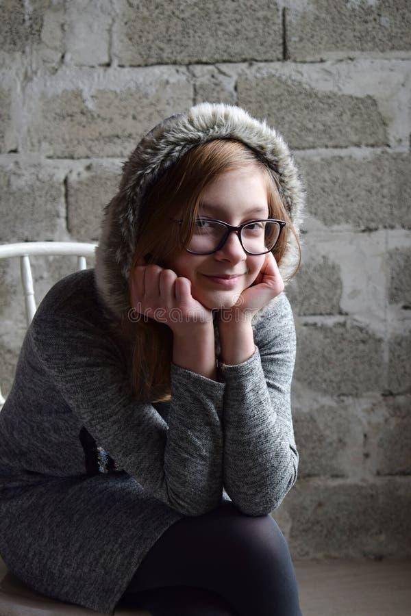 Conceptenportret van een prettige vriendschappelijke gelukkige tiener in glazen op stoel Het jonge meisje zit in een het grijze k stock foto's