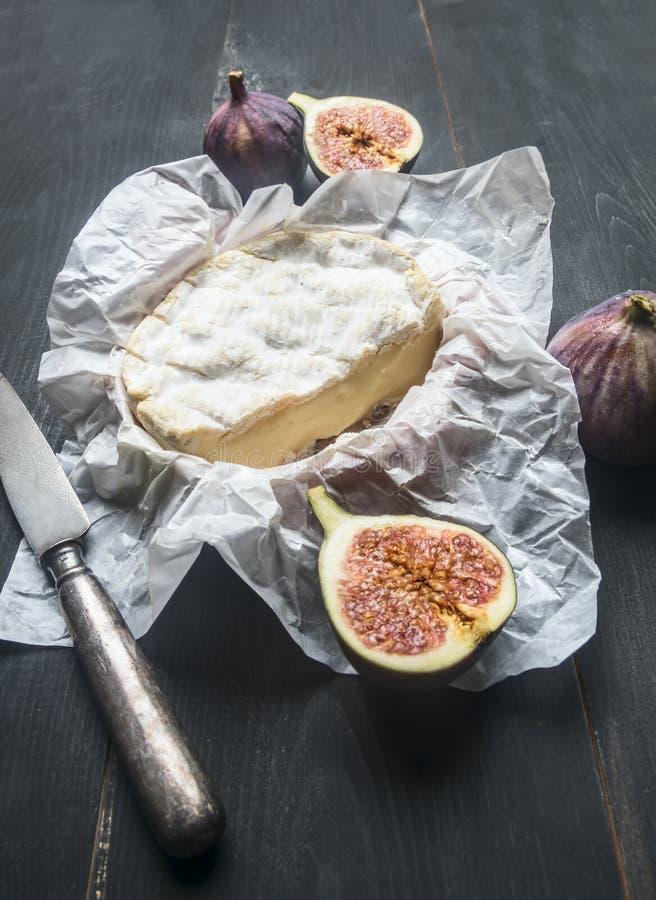 Conceptensnacks voor wijn, camembertkaas, verse gesneden fig., uitstekend lijstmes, op rustieke houten donkere achtergrond stock fotografie
