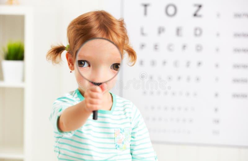Conceptenvisie het testen kindmeisje met een vergrootglas royalty-vrije stock foto