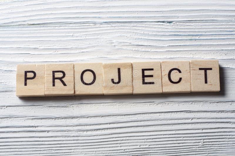 Conceptenwoord die zich met kubus op houten bureauachtergrond vormen - Project royalty-vrije stock afbeelding