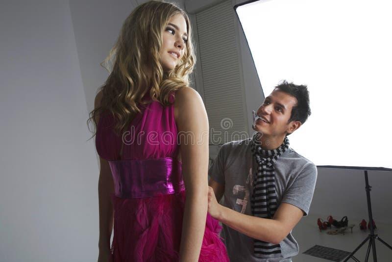 Concepteur ajustant la robe du mannequin dans le studio photo stock