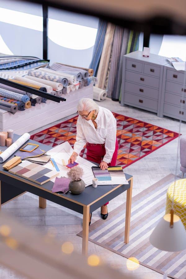 Concepteur aux cheveux blancs féminin de vieillissement principal choisissant des échantillons de tissu dans le bureau photos stock
