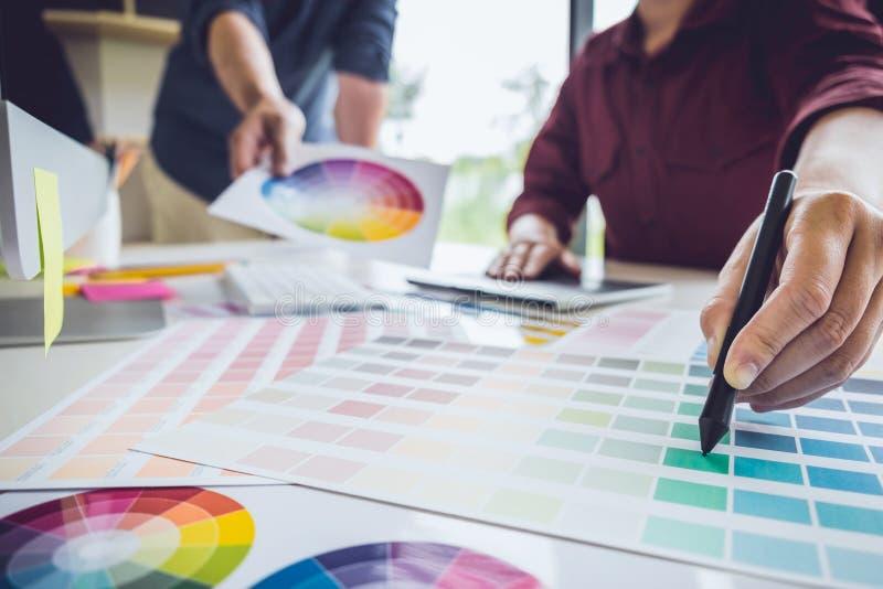 Concepteur créatif de deux collègues travaillant à la sélection des couleurs et dessinant sur la tablette graphique sur le lieu d photo libre de droits