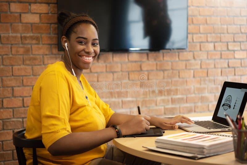 Concepteur créatif féminin africain employant le travail de comprimé graphique sur la La photo stock