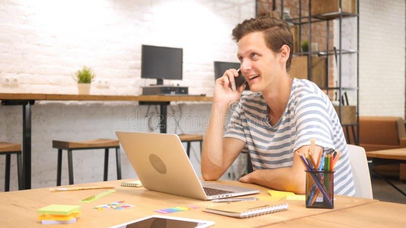 Concepteur créatif Talking au téléphone images libres de droits