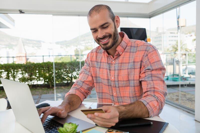 Concepteur de sourire tenant la carte de crédit tout en à l'aide de l'ordinateur portable au bureau photo libre de droits