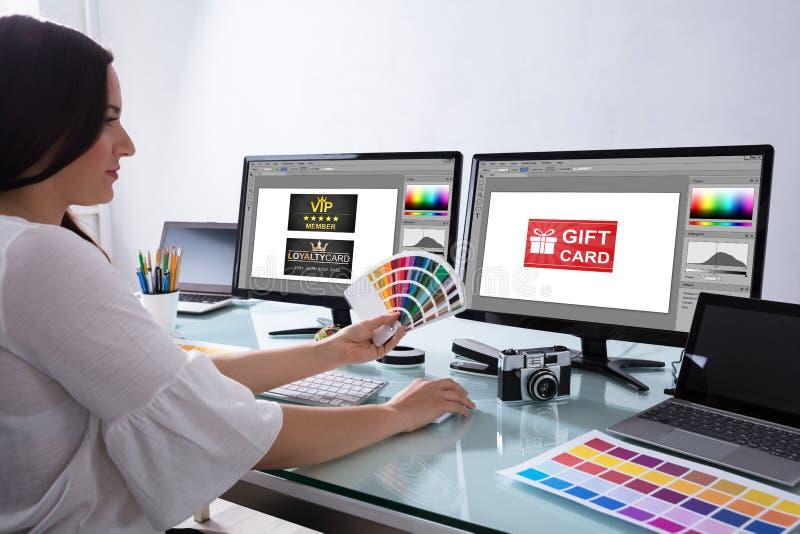 Concepteur féminin Holding Color Swatch travaillant dans le bureau images stock