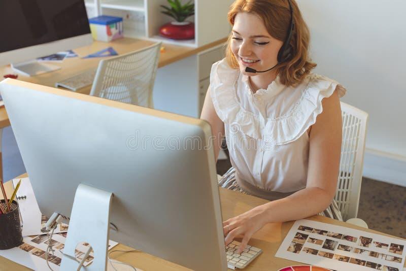 Concepteur féminin parlant sur l'écouteur tout en travaillant sur l'ordinateur au bureau photo libre de droits