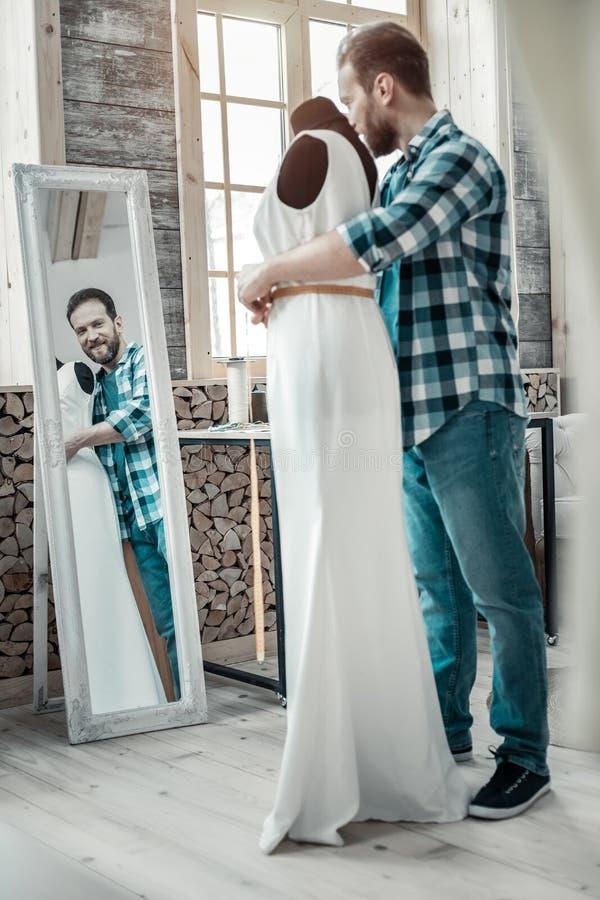 Concepteur masculin barbu faisant la mesure de la taille pour la robe images libres de droits