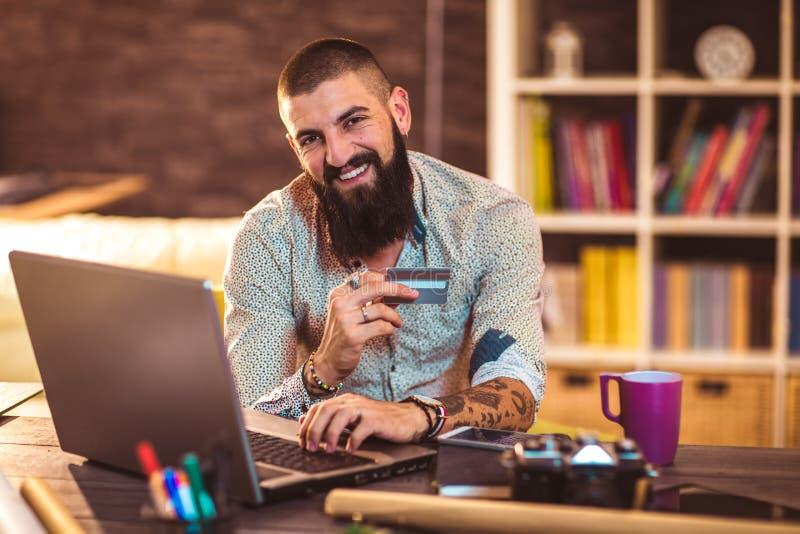 Concepteur travaillant dans le bureau utilisant la carte de crédit pour le paiement en ligne photos libres de droits
