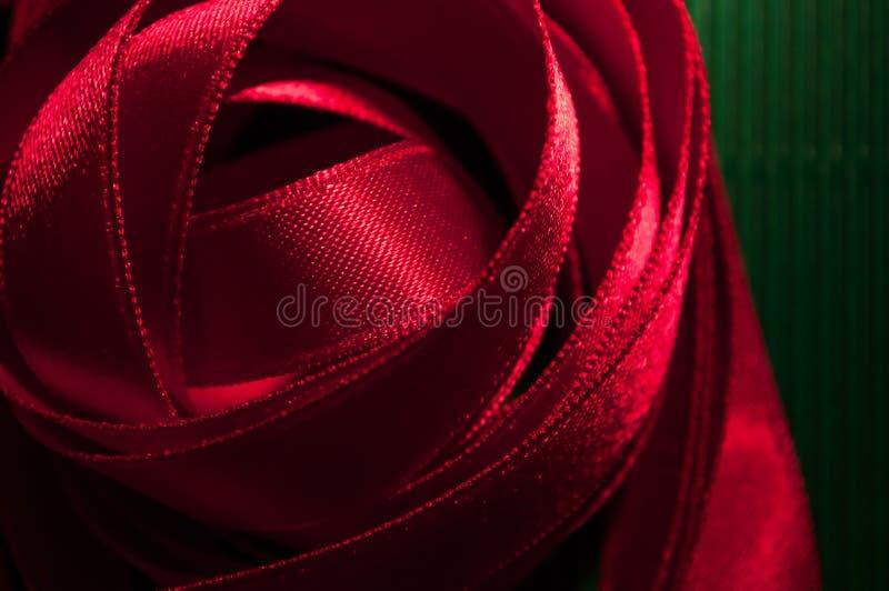 Conception bouclée de ruban rouge de plan rapproché sur la texture verte photographie stock libre de droits