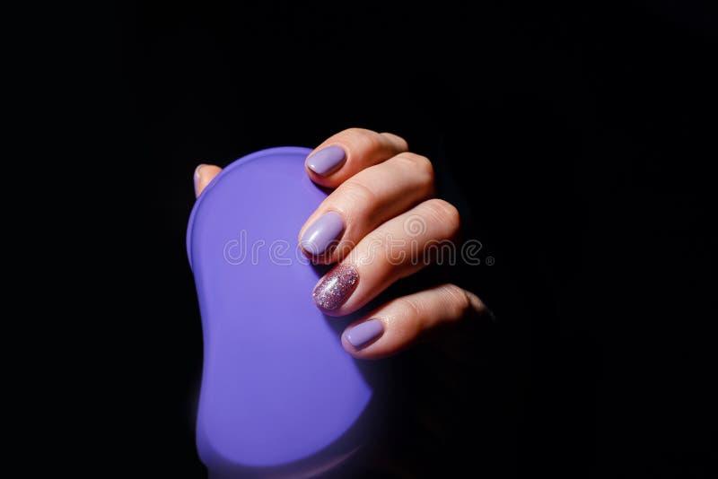 Conception de clous Mains avec la manucure lilas d'été de couleur sur Grey Background Fermez-vous des mains femelles tenant la br photographie stock libre de droits