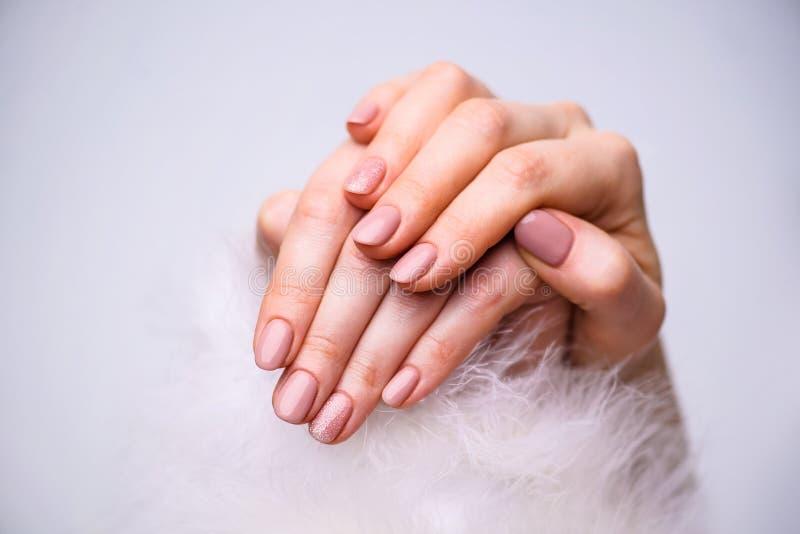 Conception de clous Mains avec la manucure rose lumineuse de ressort sur Grey Background Fermez-vous vers le haut des mains femel photos stock