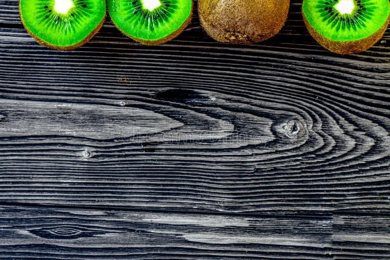 Conception exotique de fruit avec le kiwi sur la vue supérieure de fond en bois foncé image libre de droits
