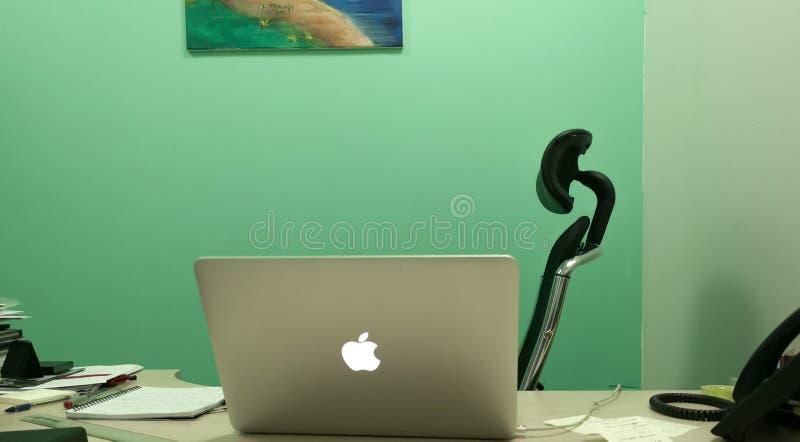 Conception intérieure d'un bureau avec des murs verts et un ordinateur portable de macbook sur le bureau - bureau naturel photos stock