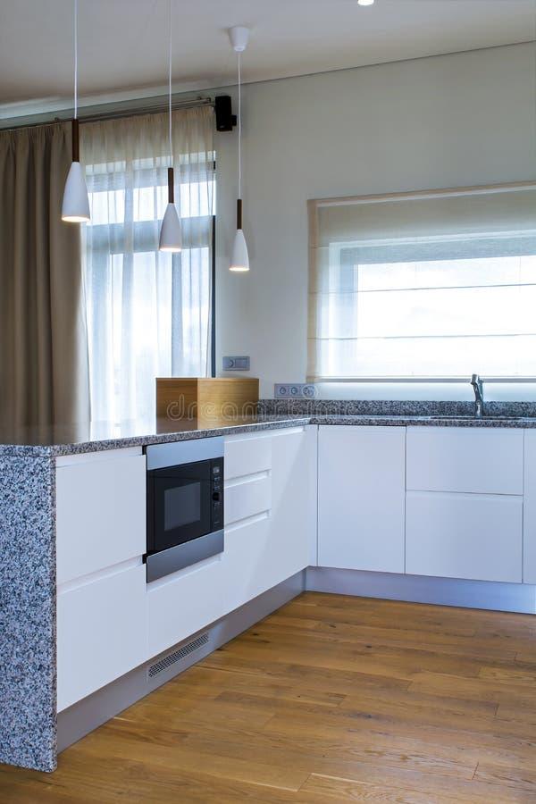 Conception moderne de cuisine dans l'intérieur léger avec les accents en bois photographie stock libre de droits